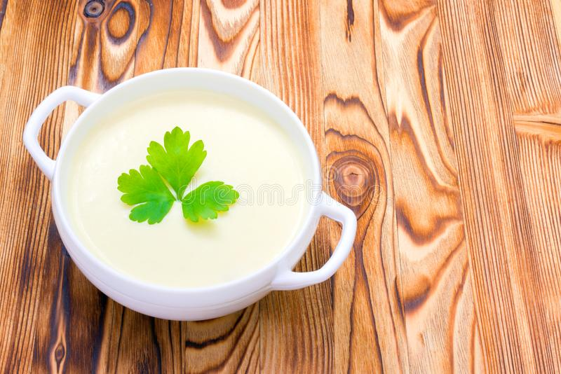 Potato and onion vegan, vegetarian healthy cream soup in white bowl. Tasty potato soup with a leaf of parsley, rustic wooden table stock photos