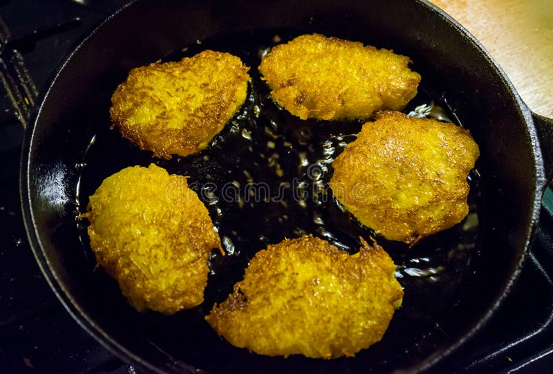 Potato pancakes, draniki, hash browns or fritters frying in old cast iron pan, skillet, selective focus royalty free stock photography