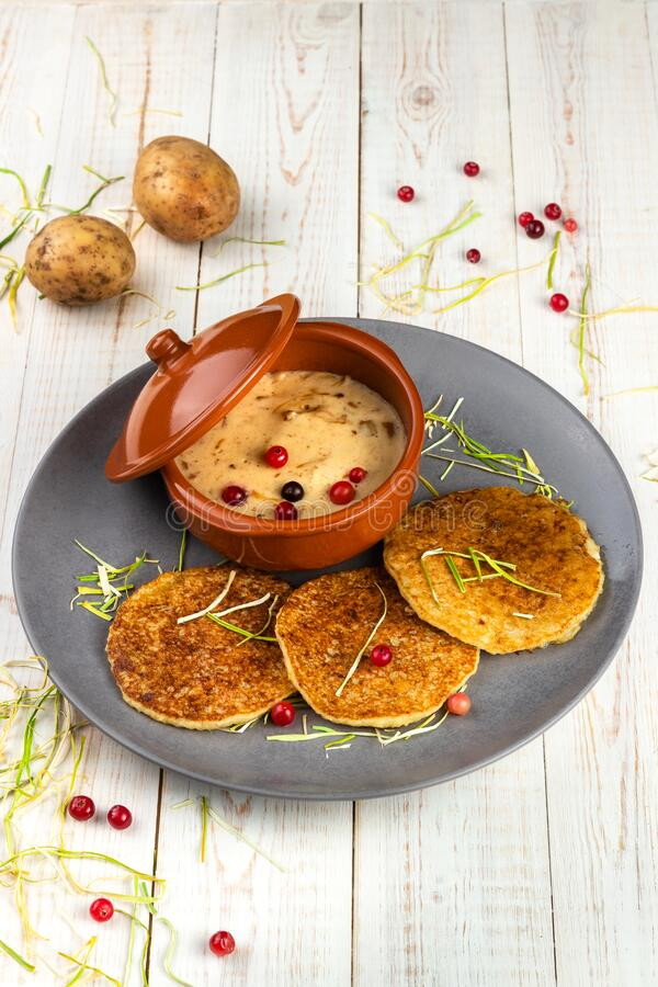 Potato pancakes and machanka with cranberries on white wooden background in rustic style, example of menu in traditional. Belarusian restaurant, vertical photo stock photography
