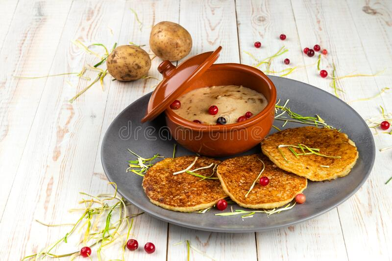 Potato pancakes and machanka with cranberries on white wooden background in rustic style, example of menu in traditional. Belarusian restaurant, horizontal stock photography