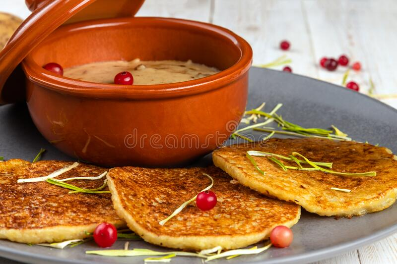 Potato pancakes and machanka with cranberries on white wooden background in rustic style, example of menu in traditional. Belarusian restaurant, close-up stock photos