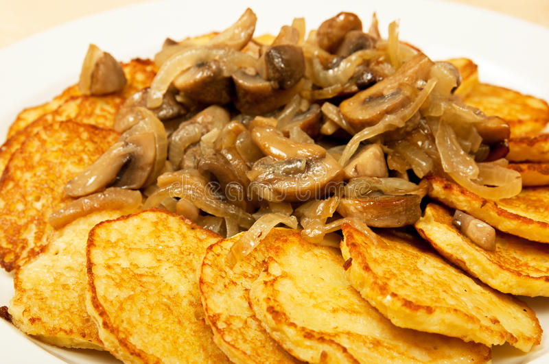 Potato pancakes with mushrooms. On the dish in restaurant stock photos