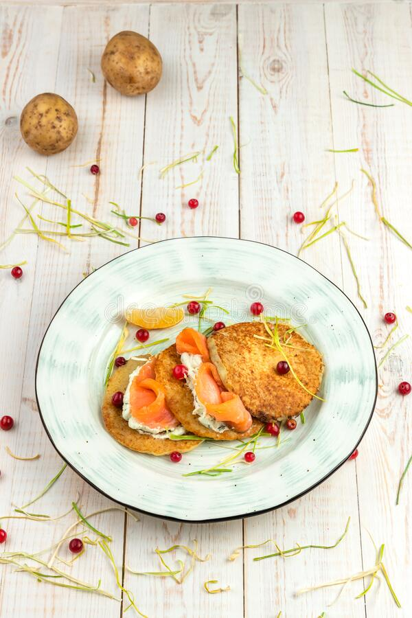 Potato pancakes with salmon, cranberries and tartar sauce on white wooden background, lunch menu of food restaurant in rustic. Style royalty free stock photography