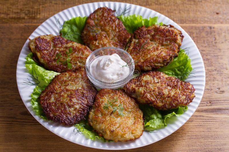 Potato pancakes with sour cream or yogurt. Vegetable fritters, latkes, draniki. Potato pancakes with sour cream or yogurt. Vegetable fritters, latkes, draniki stock images
