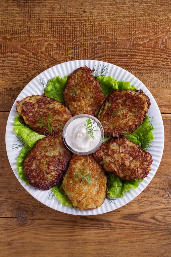Potato pancakes with sour cream or yogurt. Vegetable fritters, latkes, draniki. View from above, top studio shot stock images