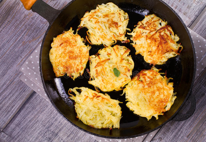 Potato Pancakes. Vegetable fritters. Latkes in frying pan. royalty free stock photography