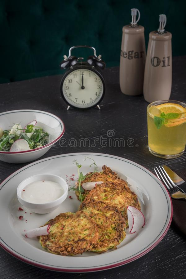 Potato pancakes on a white plate. Fresh vegetable salade and lemonade drink. Lunch time 12pm stock image