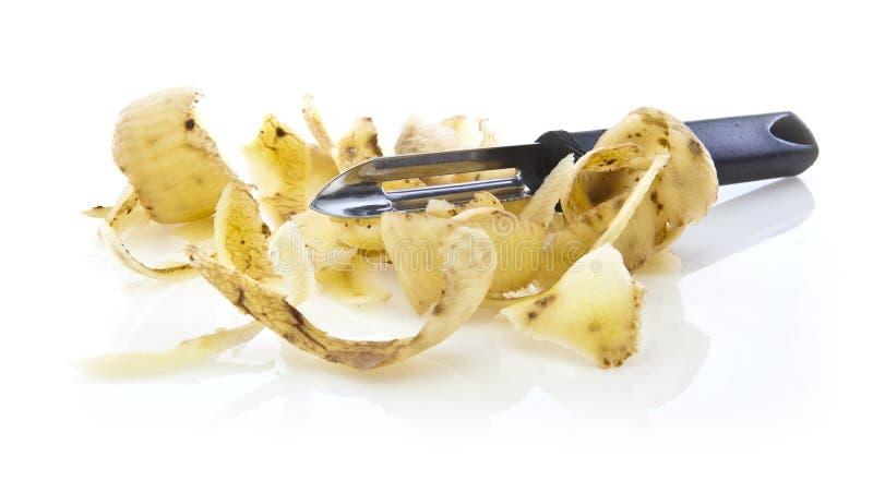 Potato peelings with peeler stock photo