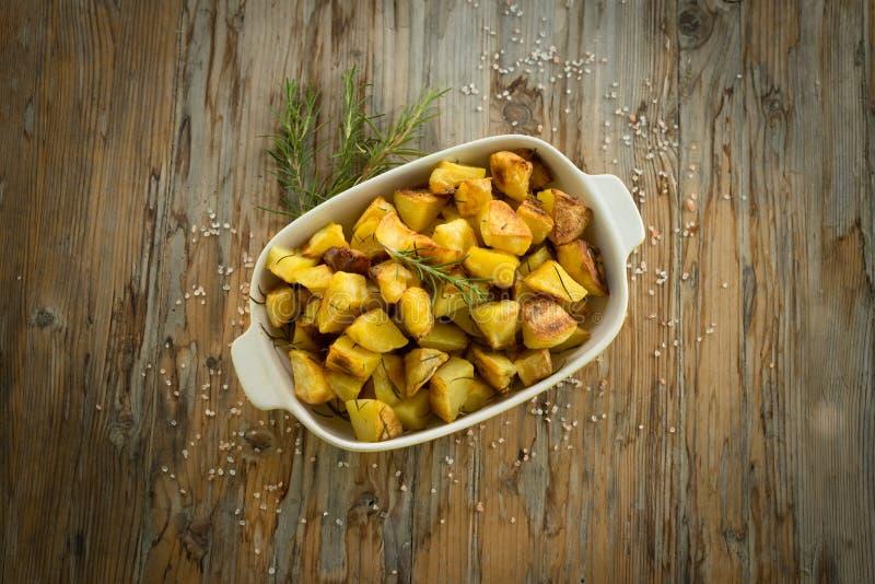 Potato roast. Tray of roasted potatoes on wooden table stock photo