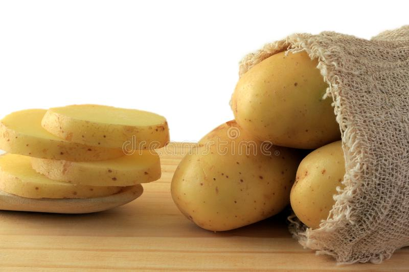 Potato sticking out of sack on wooden table, sliced potatoes in spoon. White background royalty free stock photography