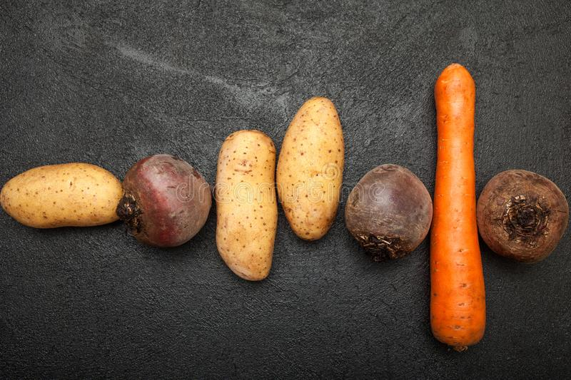 Potato tubers, beets and carrots on a black table royalty free stock photography