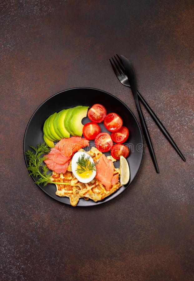 Potato waffles with vegetables. Potato waffles with salmon, egg, avocado and tomatoes on a black plate on a dark background. view from above stock image