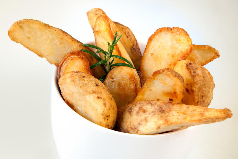 Potato Wedges. Straight from the oven, ready to eat, in a white bowl royalty free stock photography