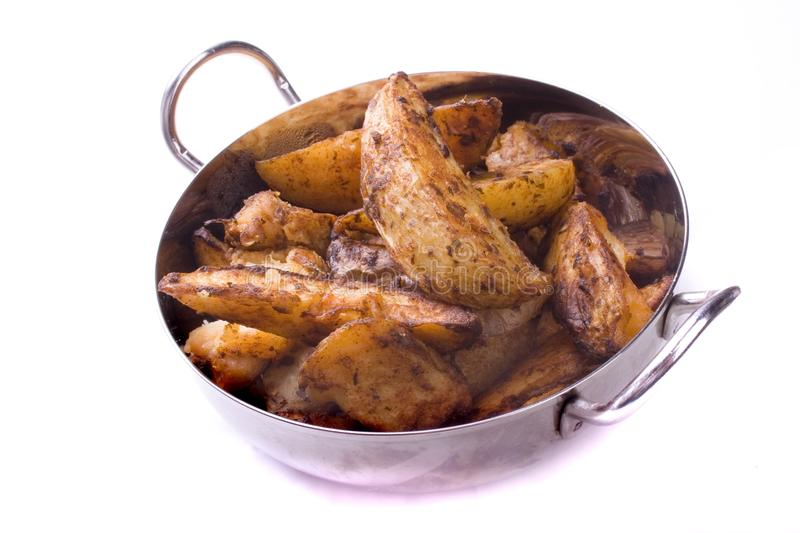Potato wedges. In a metal dish. Isolated on a white background stock image
