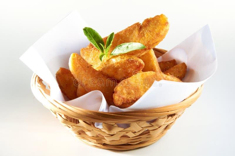 Potato Wedges. Crisp potato wedges with seasoning, fresh from the oven stock photo