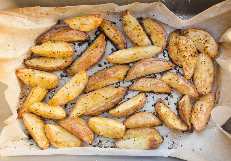 Potato Wedges. Oven baked potato wedges home made wrapped in baking paper stock photo