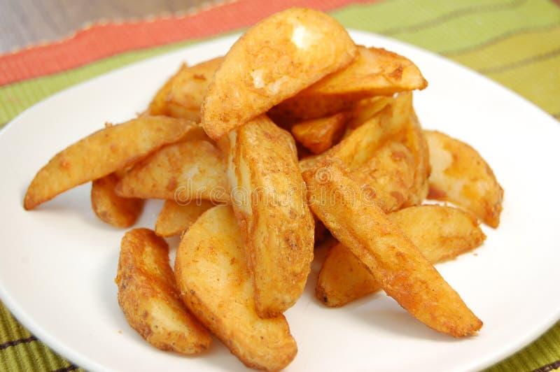 Potato wedges. Plateful of seasoned potato wedges stock photo