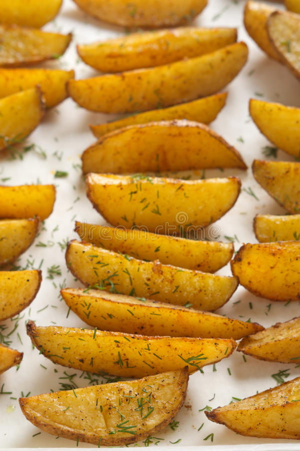 Potato wedges. Baked potato wedges with herbs decorated with dill on parchment royalty free stock image
