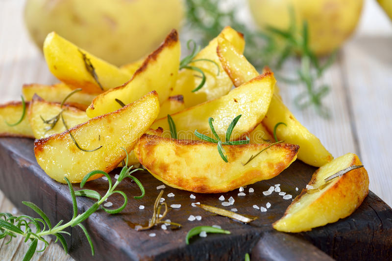 Potato wedges. Baked potato wedges with rosemary served on a shabby cutting board with potatoes in the background stock images