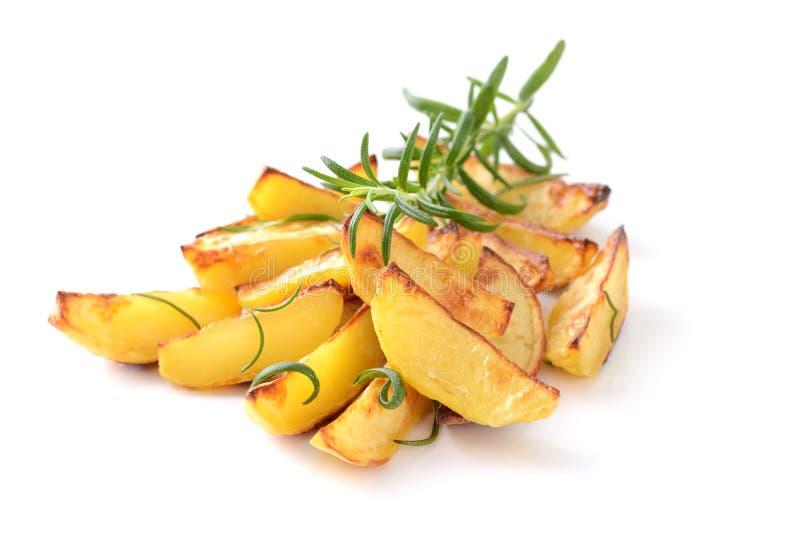 Potato wedges. Baked potato wedges with rosemary on a white background royalty free stock image