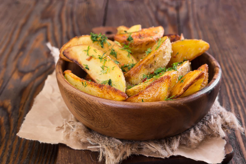 Potato wedges with dill in wooden bowl. On wooden background stock image