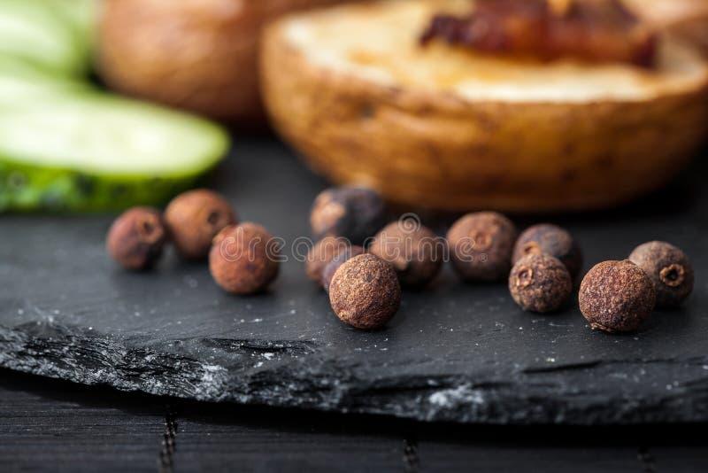 Potato wedges, peas pepper and leg of lamb. On black plate closeup stock photo