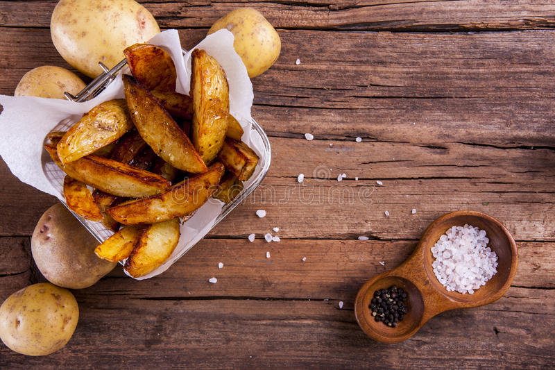 Potato wedges. Potato whole and wedges in a basket and cooking sheets with salt and pepper on wood shot from above stock photos