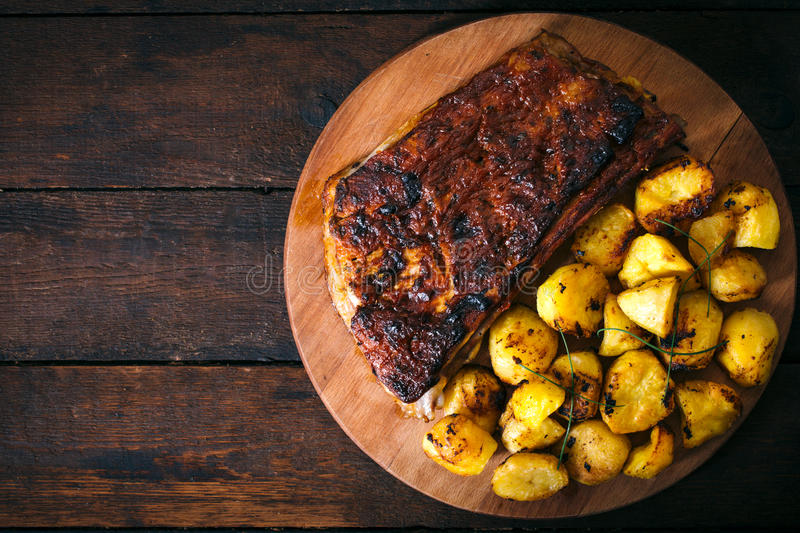 Potatoe and ribs. Baked potatoes and beef ribs in bbq sauce from above on wooden background.Blan space on the left side royalty free stock photo