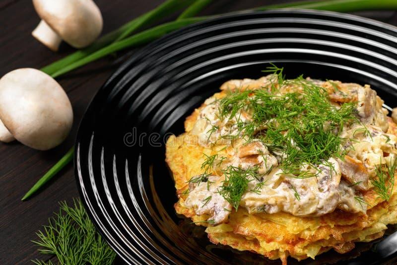 Potatoepannekoeken met champignonsaus en dille royalty-vrije stock afbeelding