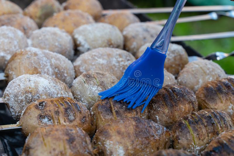 potatoes baked on the coals on the grill with a nice brown crust oiled blue tassel stock photos