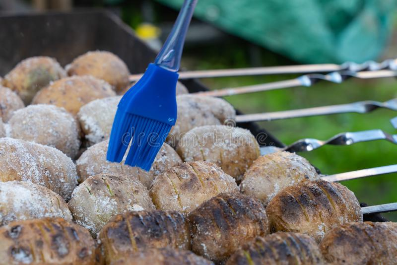 potatoes baked on the coals on the grill with a nice brown crust oiled blue tassel royalty free stock photos
