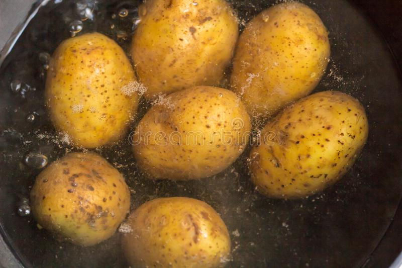 Potatoes boiling in a saucepan on a gas hob.  stock photography