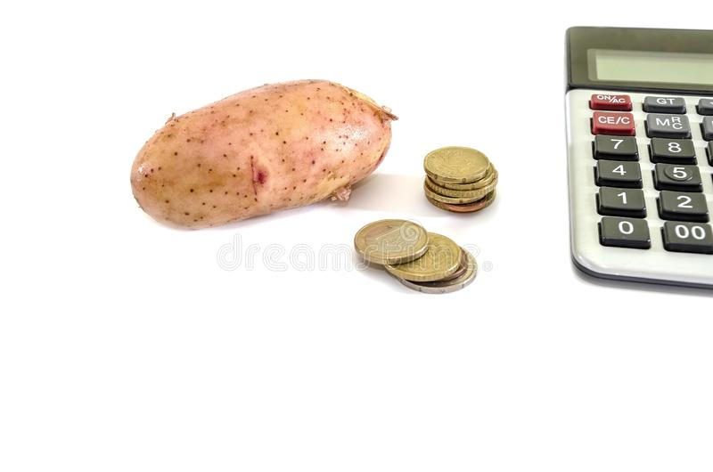 Potatoes, calculator and coins on a white background. Potatoes, calculator and coins on a white royalty free stock image