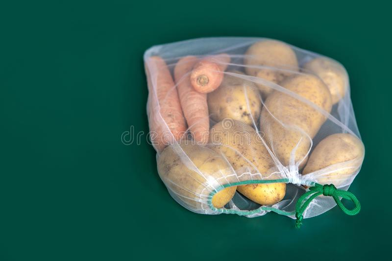Potatoes and carrots in ecological packaging. Reusable bags for vegetables and fruits. Shopping in the store. Eco-friendly stock photos