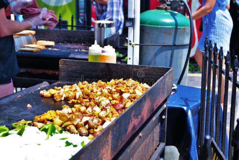 Potatoes cooking on a grill at a street fair. Potatoes cooking on a grill at street fair stock image