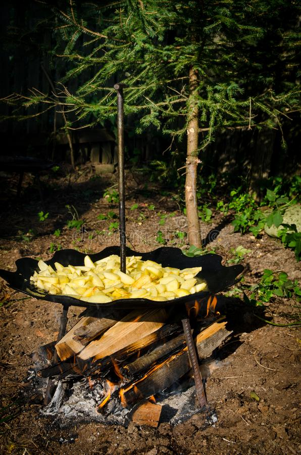 Potatoes fried in oil over a wood fire, cooked outside on unusual round curved metal steel disk. Romanian spr. Potatoes fried in oil over a wood fire, cooked royalty free stock image