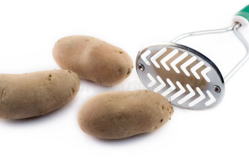Potatoes and masher stock images
