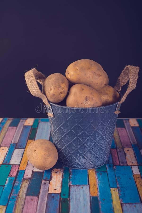 Potatoes in a metal vintage bucket. On a wooden background royalty free stock image