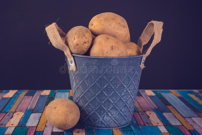Potatoes in a metal vintage bucket. On a wooden background stock photo