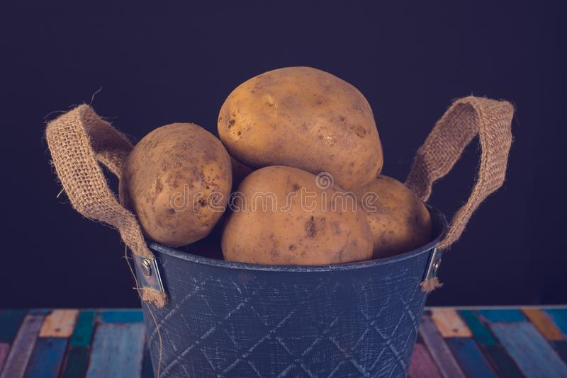 Potatoes in a metal vintage bucket. On a wooden background royalty free stock photo