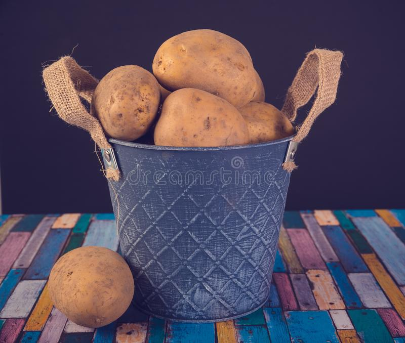 Potatoes in a metal vintage bucket. On a wooden background royalty free stock images
