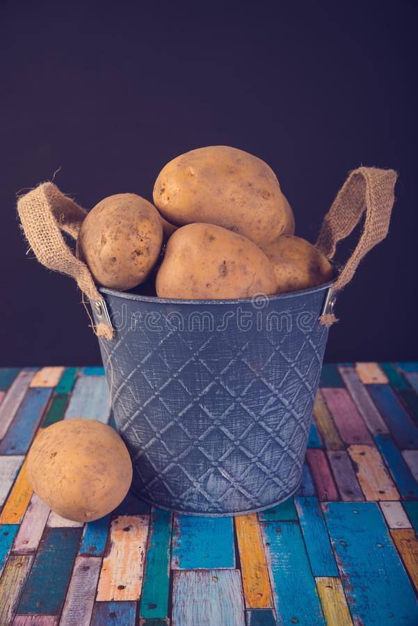 Potatoes in a metal vintage bucket. On a wooden background royalty free stock photography