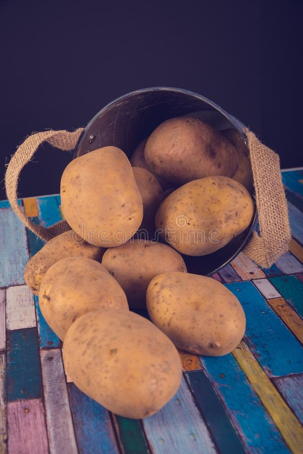 Potatoes in a metal vintage bucket. On a wooden background stock images