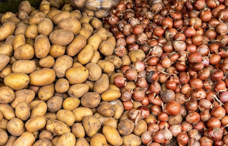 Potatoes and onions in a farmers` market. Potatoes and onions in a food market at which local farmers sell products directly to consumers royalty free stock image