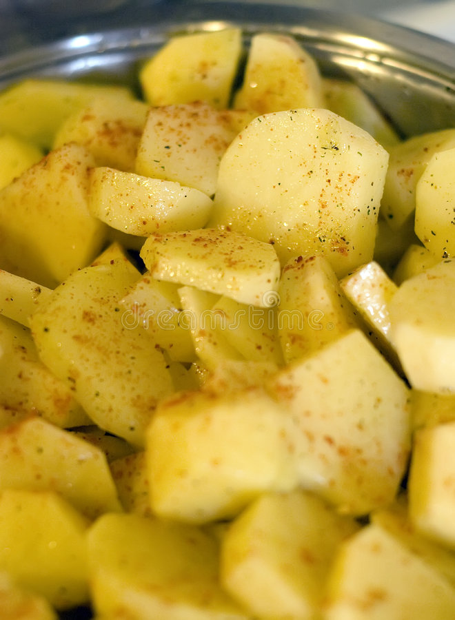 Potatoes and paprika. Some sliced potatoes with red paprika. Ready to cook in a metal pan stock photos