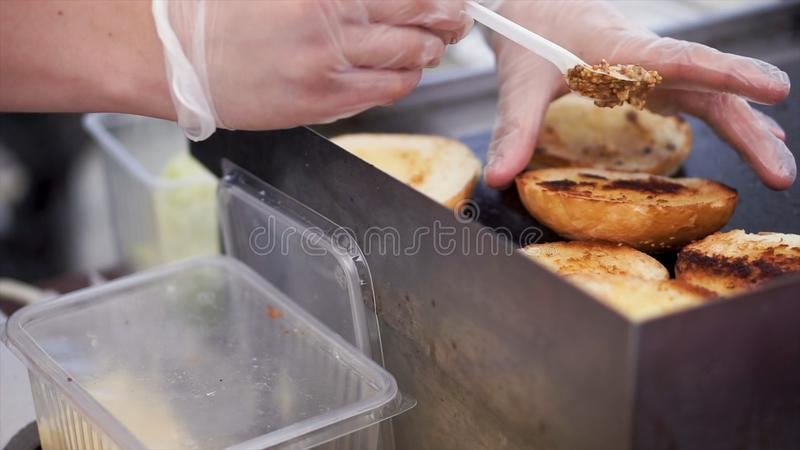Potatoes prepare on a grill. Clip. Baking potatoes on the grill, the cook lubricates the potatoes with sauce. Hand Using. Tongs For Turning potatoes on the stock images