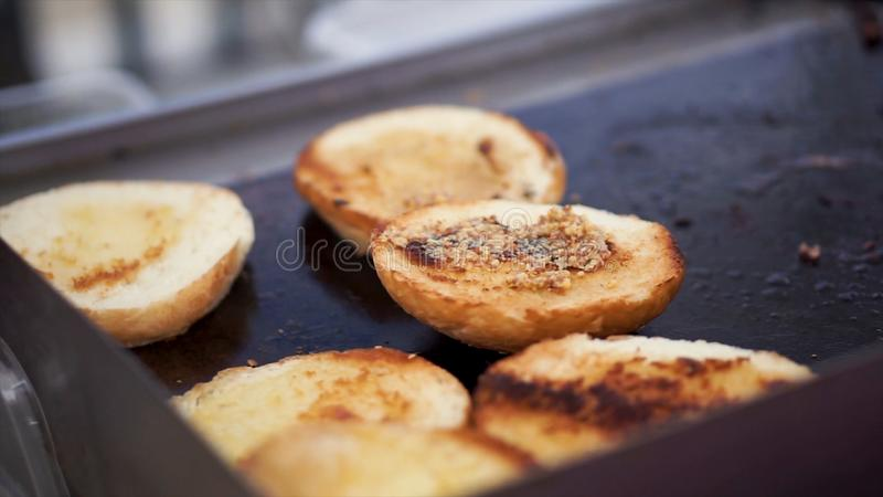 Potatoes prepare on a grill. Clip. Baking potatoes on the grill, the cook lubricates the potatoes with sauce. Hand Using. Tongs For Turning potatoes on the royalty free stock photography