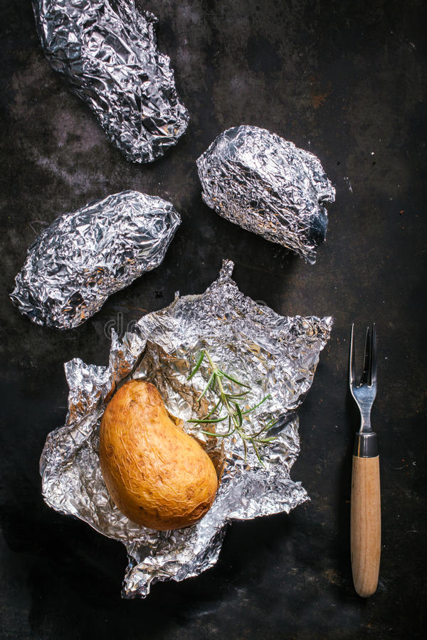 Potatoes roasted in aluminium foil. Potatoes roasted in their skin in aluminium foil on a summer BBQ being unwrapped for a tasty accompaniment to a meal or royalty free stock photos