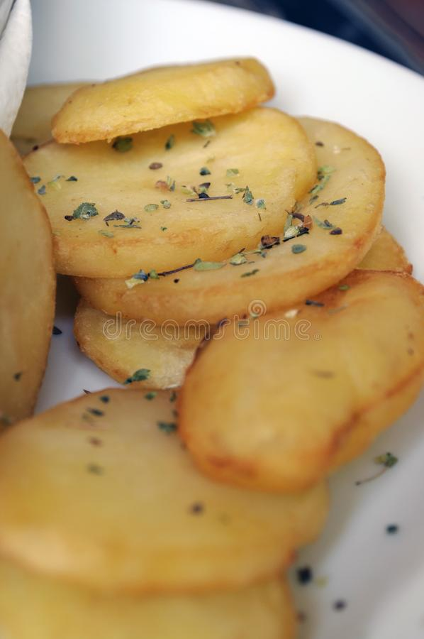 Potatoes with rosemary. Baked potatoes with rosemary in a white dish royalty free stock photography