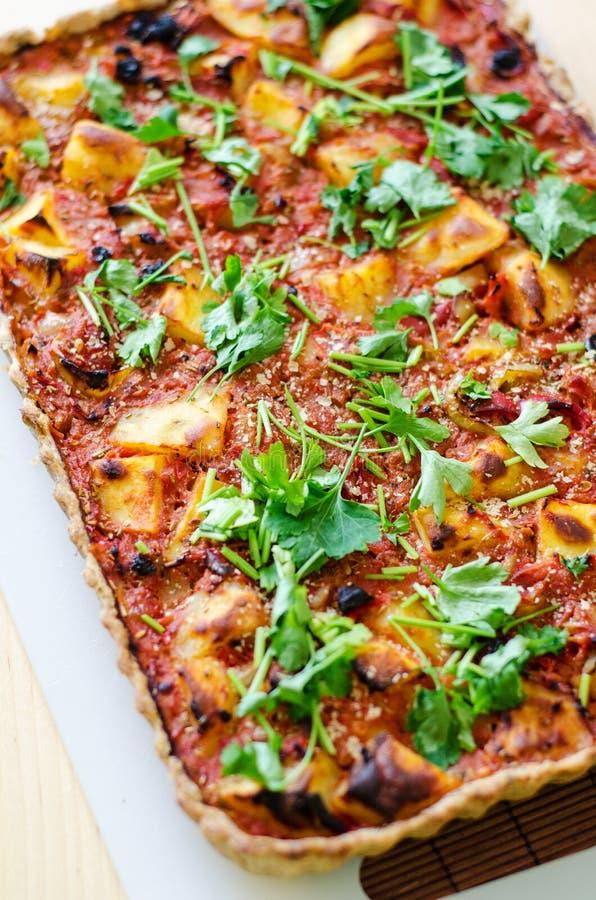 Potatoes and tomatoes vegan tart. Vegan tart with potatoes, tomatoes and parsley stock image